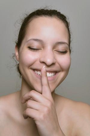 Smiling  finger on lips