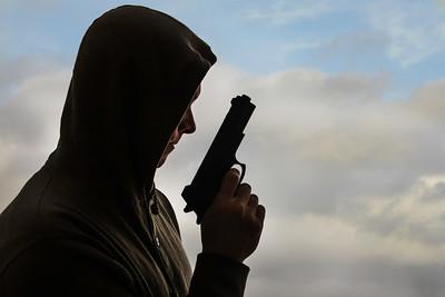 Hoodie holding a gun