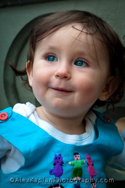 Little girl with brown hair and blue eyes wearing a blue dress with red buttons on the sleeves and green, pink and purple characters on the front of the dress looking away from the camera smiling by Alex Kaplan, photographer http://www.alexkaplanphoto.com