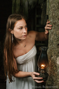 Young woman in a white dress exploring an abandoned wooden house with an oil lamp