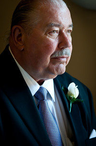 Man with mustache wearing a tuxedo and a white corsage looking into the distance Alex Kaplan Photographer https://professionalheadshots.com