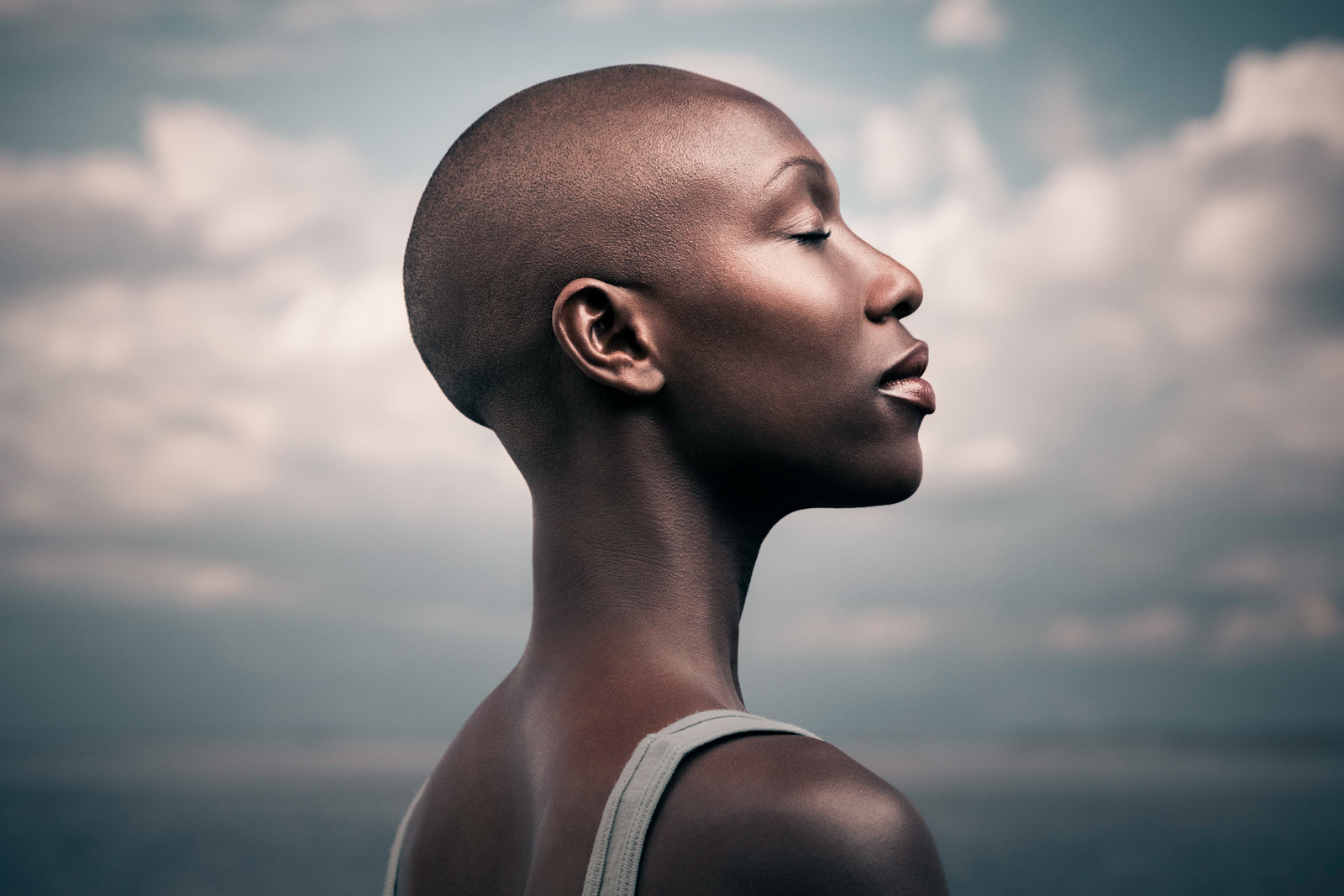 A profile of a bald African American Woman