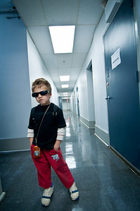 Little boy wearing red pants, black shirt and blue and white sneakers posing for the camera with sunglasses on and an orange camera around his neck in a building with blue walls and blue doors by Alex Kaplan, photographer http://www.alexkaplanphoto.com