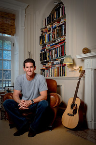 Man wearing a gray shirt and jeans smiling for the camera as he sits in a brown leather chair in front of a bookcase and next to a guitar  Alex Kaplan Photographer https://professionalheadshots.com
