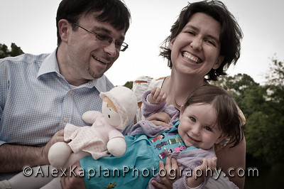 Man wearing a button down shirt holding a little girl and a doll standing with a woman all smiling for the camera Alex Kaplan Photographer https://professionalheadshots.com