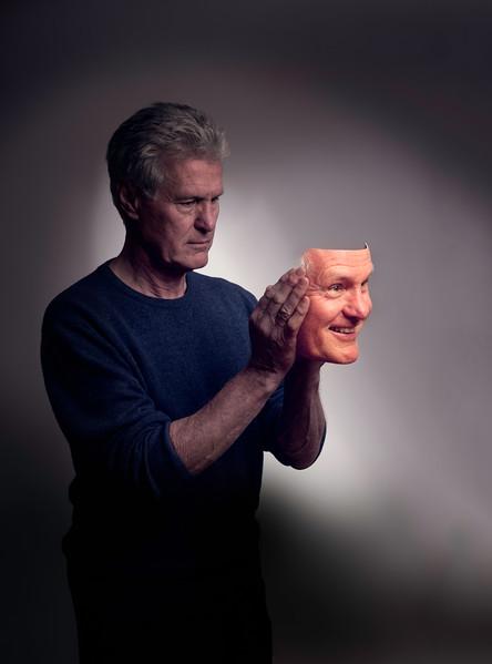 Sad man putting on a happy mask