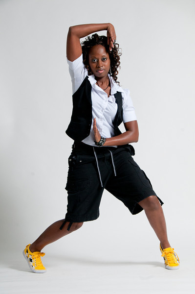 Woman wearing a white button down shirt with a black vest and black shorts and yellow sneakers posing with her hands for the camera Alex Kaplan Photographer https://professionalheadshots.com