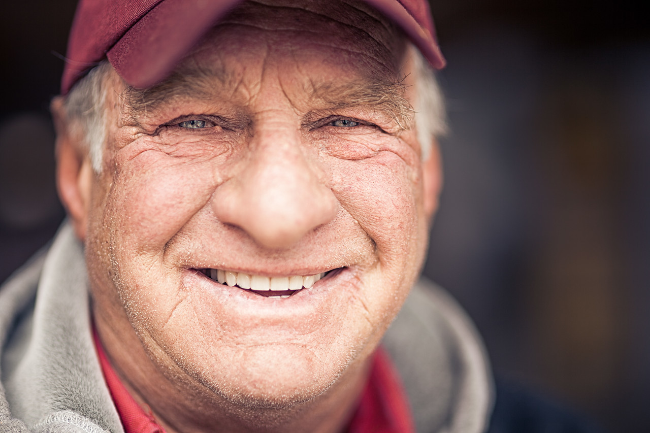 Portraiture of an older man wearing a baseball cap.