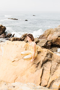 Young woman in golden space suit on matching yellow rocks on a beach