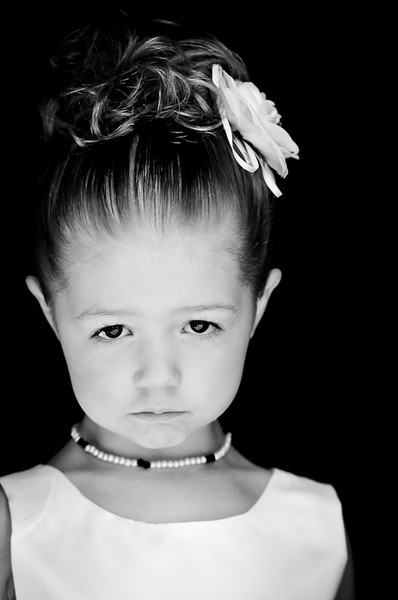 Black and white close up of a little girl wearing a dress and necklace with her hair pulled in a bun on the top of her head with a flower in her hair looking ahead by Alex Kaplan, photographer http://www.alexkaplanphoto.com