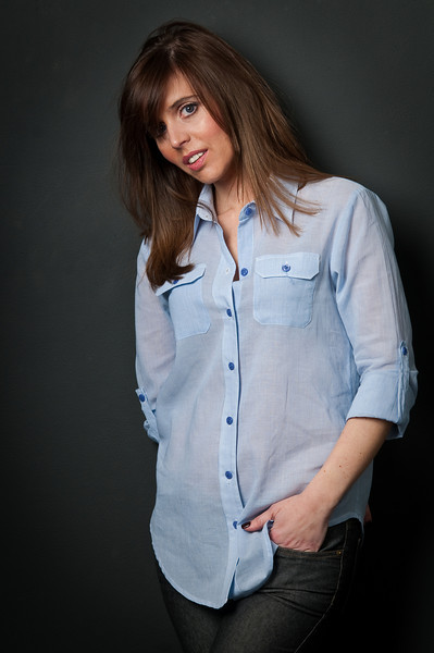 Woman with brown hair posing for the camera with her hand in her pocket and wearing a blue button down shirt  Alex Kaplan Photographer https://professionalheadshots.com