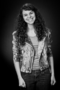 Black and white of a young girl with curly hair wearing jeans and a snakeskin jacket smiling for the camera Alex Kaplan Photographer https://professionalheadshots.com