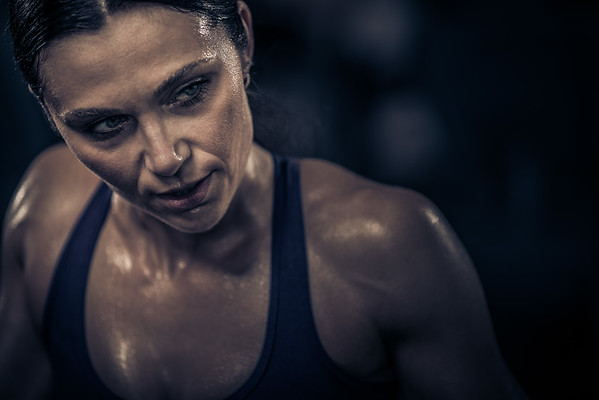A female athlete sweating and glancing to her left