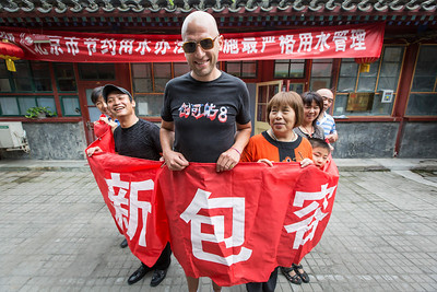 Dominic Johnson-Hill, owner of Plastered T-Shirts, poses for a portrait with locals in a hutong in Beijing September, 2013.