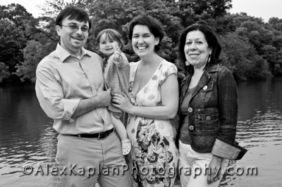 Black and white family portrait of a man holding a young girl standing with two other women all smiling for the camera Alex Kaplan Photographer https://professionalheadshots.com