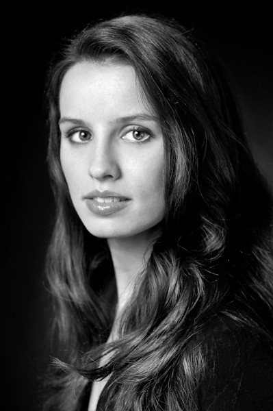 Black and white portrait of a young woman with long hair modeling for the camera Alex Kaplan Photographer https://professionalheadshots.com
