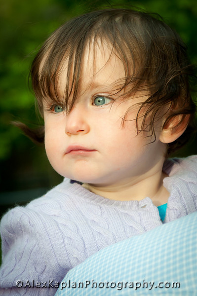 Little girl with bright blue eyes wearing a purple shirt looking off into the distance Alex Kaplan Photographer https://professionalheadshots.com