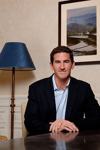 Portrait of a man in a sports jacket and blue button up shirt sitting with his hands folded on the desk in front of a blue lamp smiling for the camera  Alex Kaplan Photographer https://professionalheadshots.com