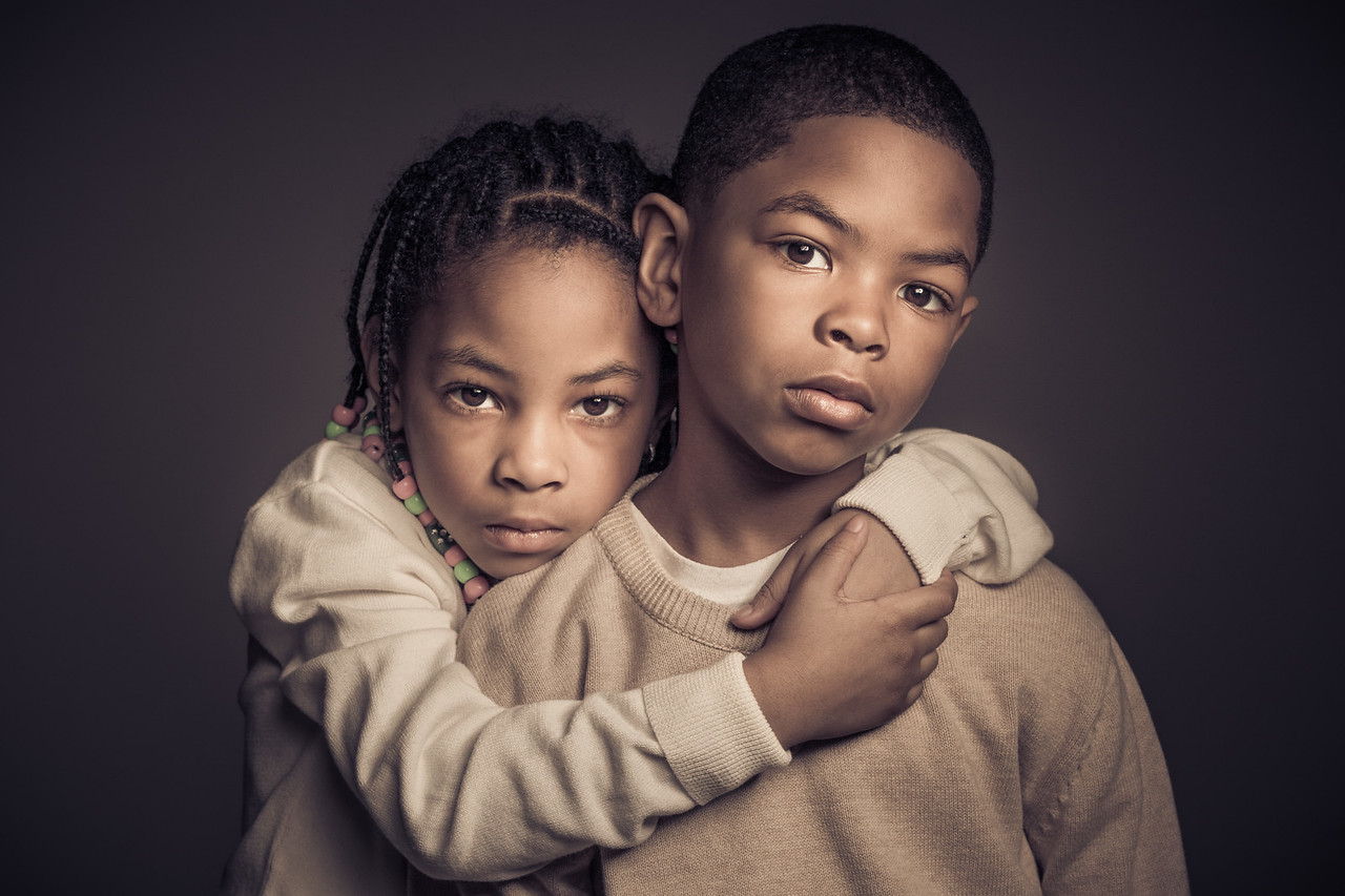 Family portrait of two African American children on charcoal.