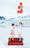 Two young women flying off a red couch on helium balloons in front of a glacier