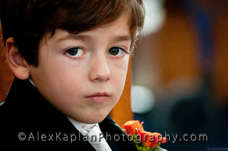 Young boy with brown hair looking at the camera wearing a tuxedo with a white vest and tie and an orange and yellow corsage by Alex Kaplan, photographer http://www.alexkaplanphoto.com