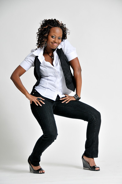 Woman wearing black pants, black heels, white button up shirt and a black vest posing with her hands on her hip for the camera Alex Kaplan Photographer https://professionalheadshots.com