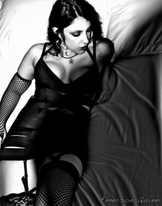 Seductive gothic temptress lies on bed in lingerie and fishnets
