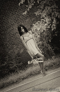Beautiful girl in nightgown walks with her burnt doll barefoot on the street