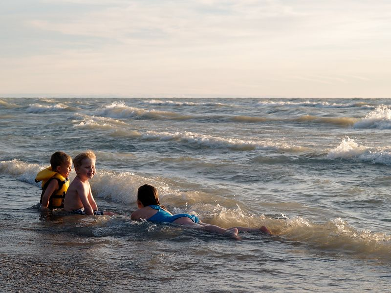 Three kids enjoying an early evening swim in Lake Huron.