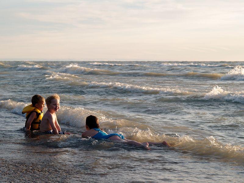 Three kids enjoying an early evening swim in Lake Huron.
