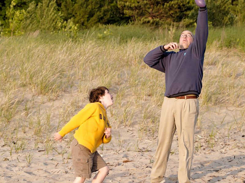 Father and son engaging in a game of football on the beach.