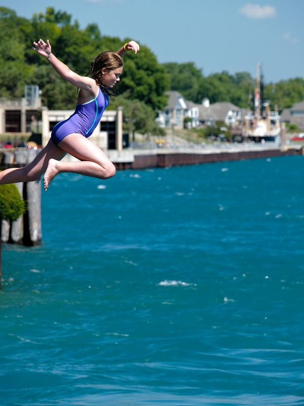 A local family celebrates the beautiful summer day by jumping off the deck of their riverside home into the St. Clair River.