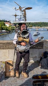 A One-Man-Band Entertains Tourists On The Charles Bridge