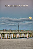 Moon rising above clouds at Pompano pier, vertical