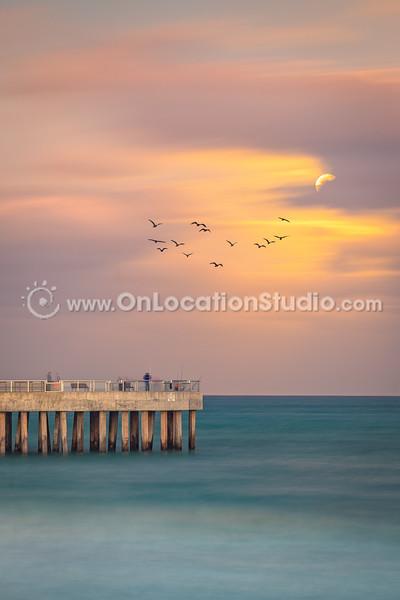 Peaking moon at pier