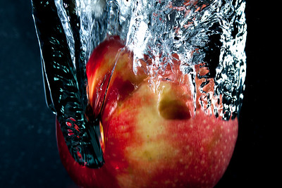 Apple in water taken with two strobes at 1/5000s to freeze motion