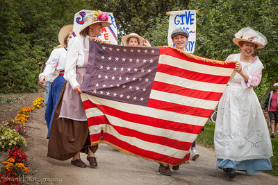 A group of suffragettes marches in the re-enactment of a 1910s 4th of July parade.
