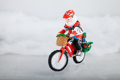 A figurine of Santa Claus delivers packages through ice and snow.