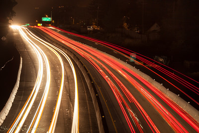 Car light make trails in a long exposure from a bridge over Highway 1.