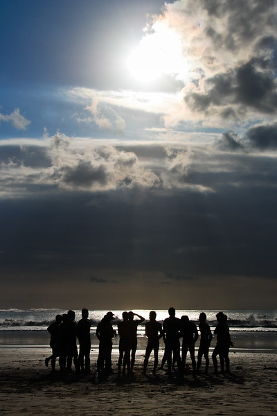 This is on Kuta beach in Bali. A group of lifeguards in training were taking some instruction as the sun broke out of the clouds.