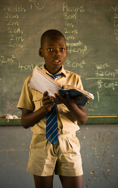 African school boy. This poor kid was called to read a passage in front of the class. The teacher showed no mercy as she tossed insult after insult at his earnest but poor reading ability.