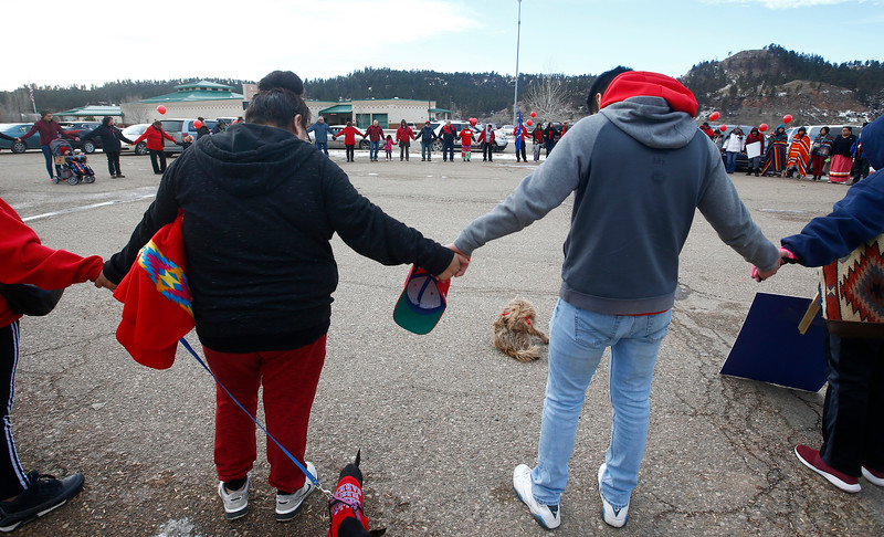 Community members join hands in the parking lot of the Northern Cheyenne Agency Bureau of Indian Affairs before marching to the Chief Little Wolf Capitol Building in Lame Deer, Mont. on Wednesday, January 9, 2019. The aim of the march, scheduled on Scott's birthday, was to call for justice for the teenager's death.