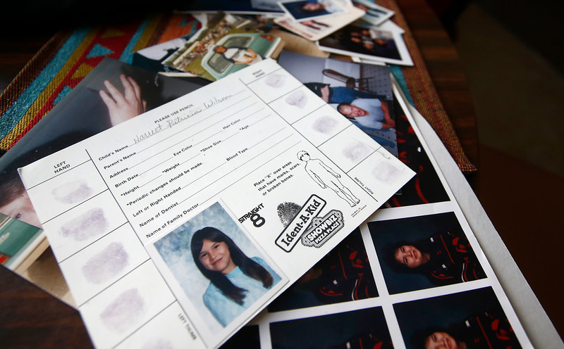 A card with the fingerprints and a photo of a young Harriet Wilson lays on a table beside a box of old photos in Mary Wilson's home in Billings, Mont. on Friday, March 1, 2019.