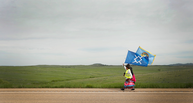 Supporters carry tribal flags as they walk across the Crow Reservation to raise awareness for Missing and Murdered Indigenous People near Crow Agency, Mont. on Saturday, May 27, 2018.