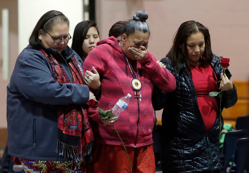 Two women support Paula Castro, middle, the mother of Henny Scott, as she walks to view her daughter in her casket for the final time during the funeral service at Lame Deer High School in Lame Deer, Mont. on Saturday, January 5, 2019.