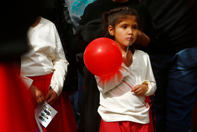 A girl holds a red balloon as she waits to march to the lawn of the Yellowstone County Courthouse for the Missing and Murdered Indigenous Women's March in Billings, Mont. on Friday, April 5, 2019.