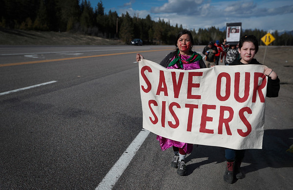 Two women carry a sign that reads 'Save our sisters' as they walk along Hwy. 93 during Marita Growing Thunder's annual 80-mile trek across the Flathead Indian Reservation to raise awareness for Missing and Murdered Indigenous Women north of Arlee, Mont. on Sunday, March 31, 2019.