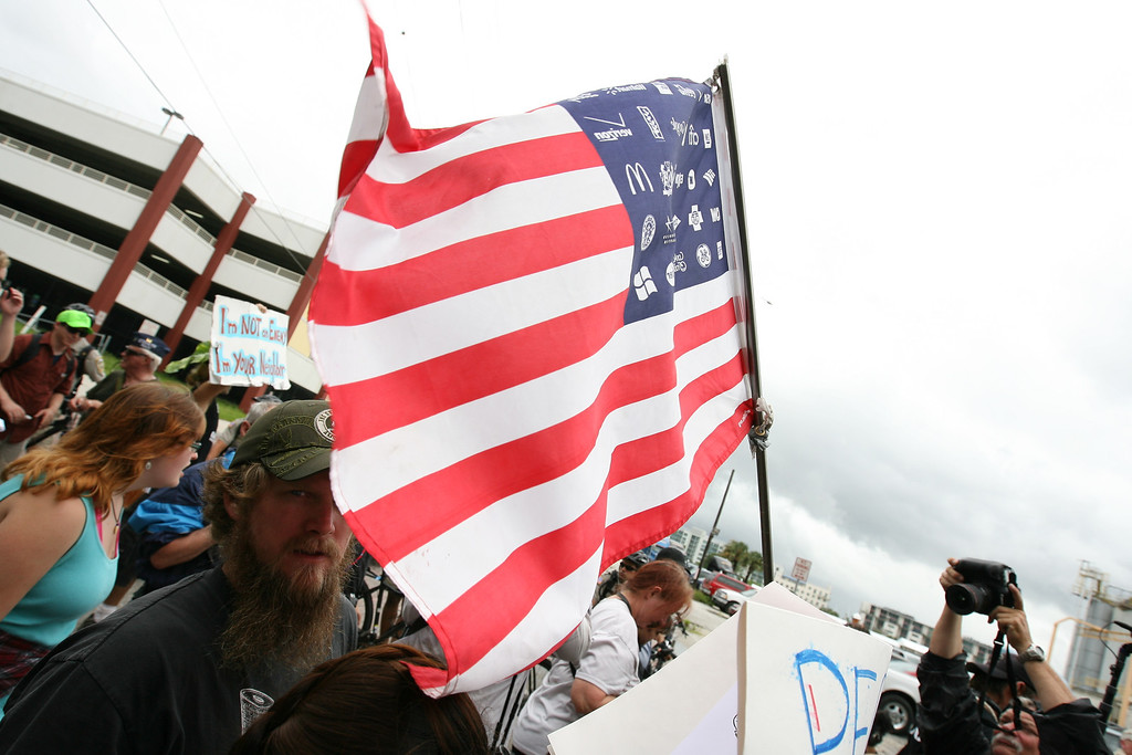 This take on the American flag, carried by protesters throughout the Coalition March on the RNC, displays corporate logos instead of the traditional stars of the states.  Tampa, Florida. August 27th, 2012.