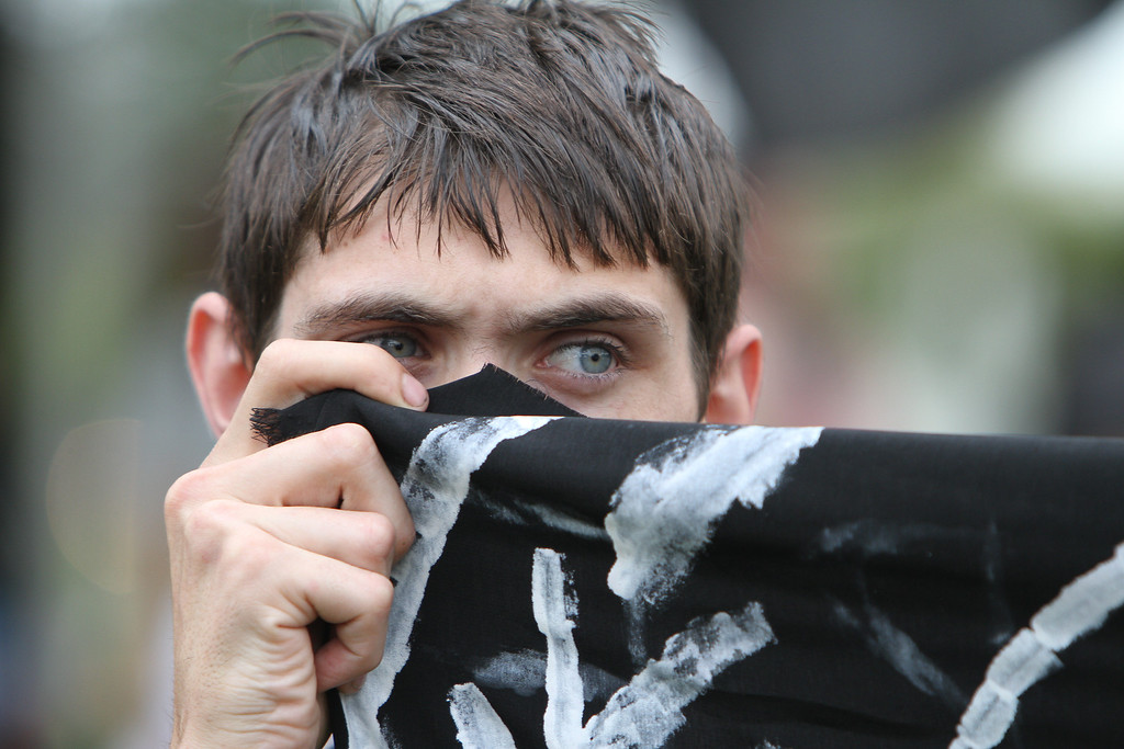 A member of the black bloc covers his face in front of cameras as protesters prepare for the Coalition March on the RNC, August 27th, 2012 in Tampa, Florida.  Activists gathered from around the country to attend the protests, but many were absent due to the approach of Hurricane Isaac.