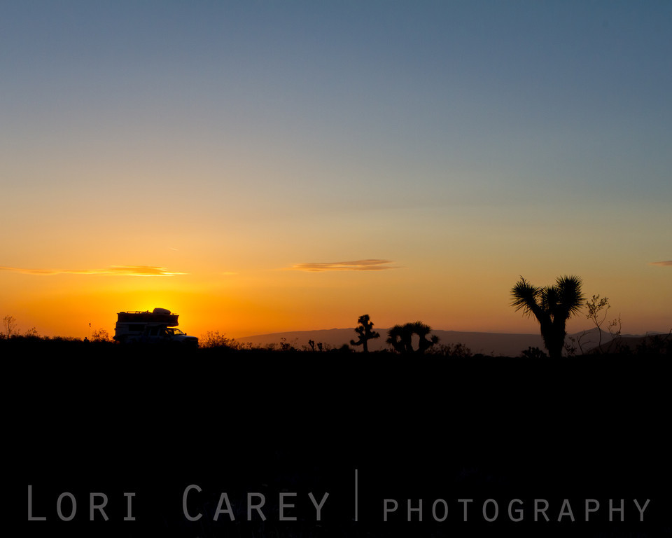 Expedition vehicle silhouetted in desert at sunset
